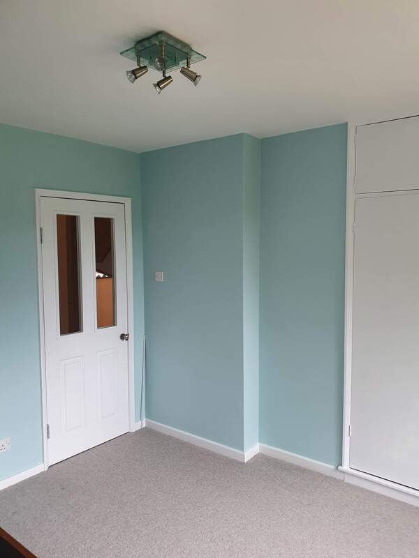 Picture of the walls and door to a master bedroom. The walls are painted in duck egg and the door and skirting boards have been glossed in white
