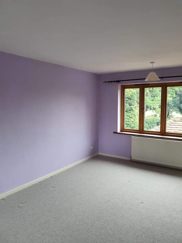 Picture of a bedroom that has been redecorated in a lilac emulsion and the skirting boards have been glossed in white. The window on the back wall of the bedroom looks to the rear garden and natural daylight is coming into the room.